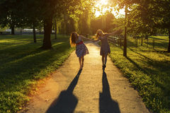 Dos novias de las chicas jóvenes van juntas a lo largo del parque en los rayos del contraluz del sol poniente Fotografía de archivo libre de regalías