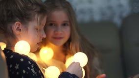 Dos novias del juego de la colegiala con las guirnaldas luminosas por la tarde en casa Iluminación casera, de niña metrajes