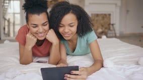 Dos novias divertidas de la raza mixta alegre que comparten medios sociales usando la tableta y las negociaciones que mienten en  almacen de video
