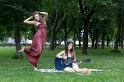 Dos novias elegantes elegantes del boho feliz con la guitarra, comida campestre Imagen de archivo libre de regalías