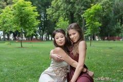 Dos novias elegantes elegantes del boho feliz meriendan en el campo en parque Foto de archivo