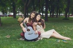 Dos novias elegantes elegantes del boho feliz con la guitarra, comida campestre Foto de archivo
