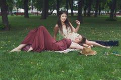 Dos novias elegantes elegantes del boho feliz con la guitarra, comida campestre Fotos de archivo libres de regalías