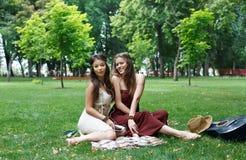 Dos novias elegantes elegantes del boho feliz meriendan en el campo en parque Fotos de archivo