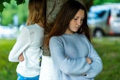Dos novias en el verano en un parque en naturaleza Ofendido Los amigos pelearon Negativa entre las muchachas Imagen de archivo libre de regalías