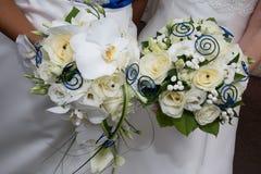Dos novias en el vestido de boda que coloca y que sostiene el ramo fotos de archivo