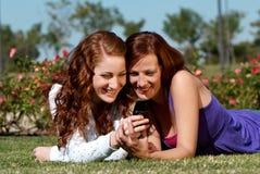 Dos novias en parque con un teléfono móvil Fotos de archivo libres de regalías