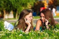 Dos novias en parque con un teléfono móvil Imagen de archivo libre de regalías