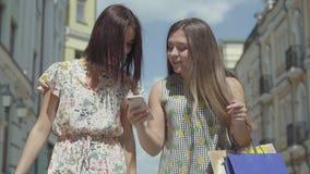 Dos novias felices después de hacer compras con los bolsos de compras delante de edificios hermosos que discuten las noticias que almacen de video
