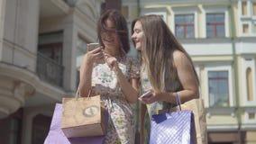 Dos novias felices después de hacer compras con los bolsos de compras que mandan un SMS en el teléfono móvil delante de edificios metrajes