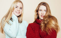 Dos novias jovenes en los suéteres del invierno dentro que se divierten lifestyle Los amigos adolescentes rubios se cierran para  fotos de archivo