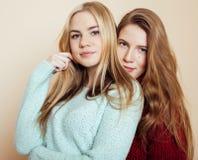 Dos novias jovenes en los suéteres del invierno dentro que se divierten lifestyle Los amigos adolescentes rubios se cierran para  imagen de archivo