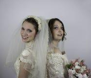Dos novias jovenes que se colocan de nuevo a la parte posterior Imagen de archivo