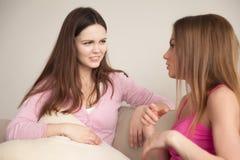 Dos novias jovenes que tienen conversación personal Imagen de archivo