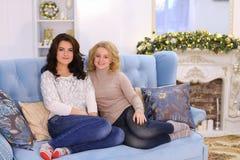 Dos novias lindas que presentan con sonrisa y que se sientan junto en c Fotos de archivo