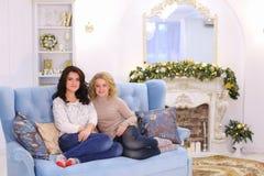 Dos novias lindas que presentan con sonrisa y que se sientan junto en c Foto de archivo