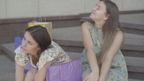Dos novias lindas que se sientan en las escaleras después de hacer compras con los bolsos de compras Las señoras son cansadas y a almacen de video