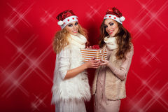 Dos novias magníficas con el brillo sonríen los sombreros de Papá Noel que llevan y calientan las bufandas de lana que dan la act Imagen de archivo libre de regalías