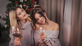 Dos novias multirraciales atractivas, presentando delante de la cámara con los vidrios y el vino grandes en sus manos En el fiche almacen de video