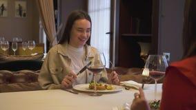 Dos novias positivas que se sientan en el restaurante moderno, junto Las muchachas que hablan la charla tienen conversación en metrajes