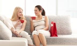 Dos novias que charlan con las tazas de café en el sofá Fotografía de archivo