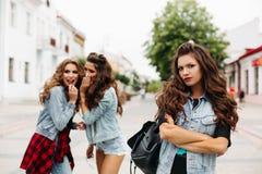 Dos novias que cotillean sobre tercero en la calle Fotografía de archivo