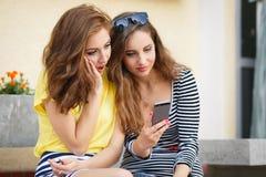 Dos novias que miran las fotos en el teléfono móvil Fotografía de archivo libre de regalías