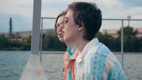 Dos novias que se relajan por la charca que se sienta al borde de un embarcadero de madera y que habla el uno al otro Día de vera