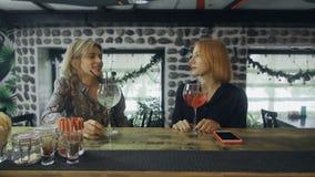 Dos novias que se sientan cerca de contador de la barra con los cócteles del alcohol que tienen conversación interesante almacen de video