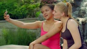Dos novias que toman las fotos en parque Selfie de las muchachas al aire libre Novias felices almacen de video