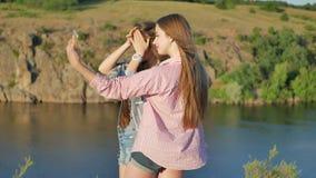 Dos novias que toman las fotos en parque Selfie de las muchachas al aire libre metrajes
