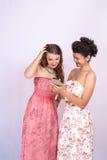 Dos novias reaccionan emocionalmente a la información en el smartphone Tecnología, Internet, comunicación Foto de archivo libre de regalías