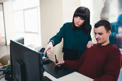 Dos oficinistas jovenes hermosos que miran un monitor de computadora y discuten el proyecto La situación en la oficina Foto de archivo