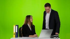Dos oficinistas que se ríen de lo que él vio en el ordenador portátil metrajes
