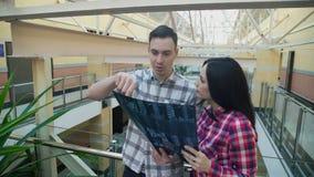 Dos oficinistas se colocan en pasillo y examinan imagen del rayo de X almacen de metraje de vídeo