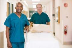 Dos ordenanzas que empujan la cama abajo de un pasillo del hospital Foto de archivo