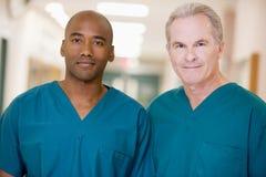 Dos ordenanzas que se colocan en un pasillo del hospital imagen de archivo libre de regalías