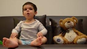 Dos a?os lindos del muchacho que ve la TV con su oso de peluche almacen de video