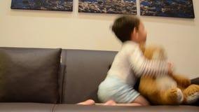 Dos a?os lindos del muchacho que ve la TV con su oso de peluche almacen de metraje de vídeo