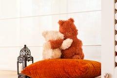 Dos osos de peluche de amor del abarcamiento que miran a través de la ventana Fotografía de archivo