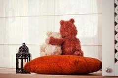 Dos osos de peluche cariñosos del abarcamiento que se sientan en ventana-travesaño. Foto de archivo