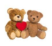 Dos osos de peluche felices con un corazón rojo aislado en el backgro blanco Imagen de archivo libre de regalías
