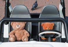 Dos osos de peluche se están sentando detrás de la rueda de un coche del juguete fotos de archivo libres de regalías