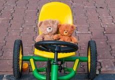 Dos osos de peluche se están sentando detrás de la rueda de un coche del juguete imagen de archivo