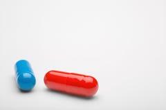 Dos píldoras médicas azules y rojas con sombras imagenes de archivo