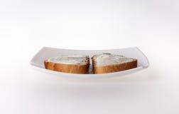 Dos paces del pan con el queso cremoso en la placa blanca Fotos de archivo