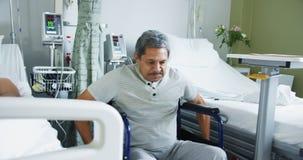 Dos pacientes masculinos que hablan en una sala de hospital 4k almacen de metraje de vídeo