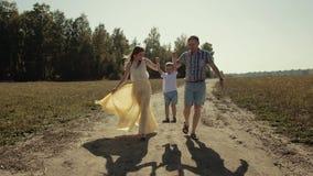 Dos padres jovenes que corren deteniendo a su hijo son manos para levantarlo hasta el aire almacen de metraje de vídeo