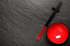 Dos palillos y placa roja en fondo de piedra negro Fotos de archivo libres de regalías
