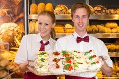 Dos panaderos que sostienen la bandeja con los bocadillos en la tienda del panadero imagenes de archivo